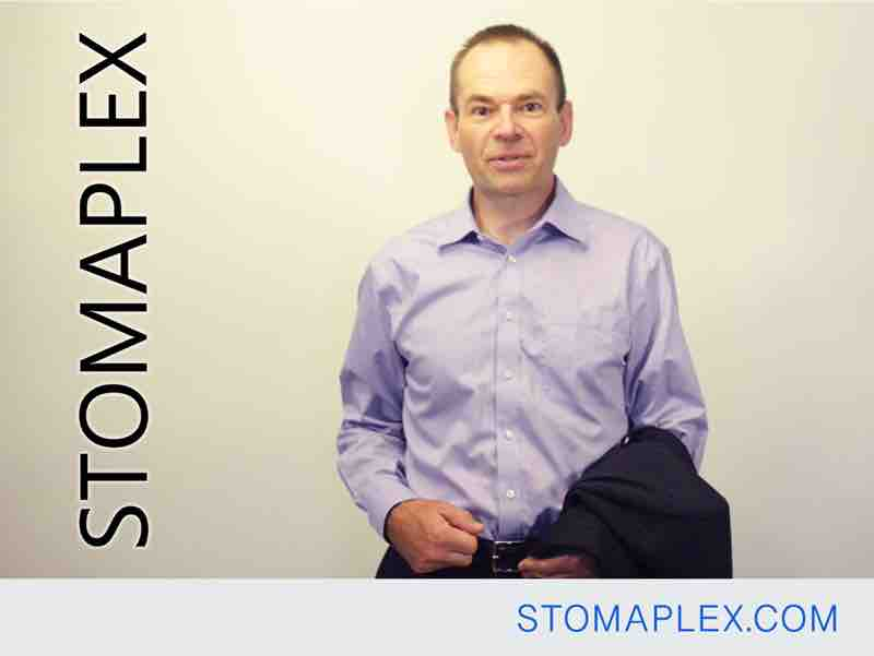 mens ostomy clothing, stomaplex stoma guard is hit with a hand after man is dressed with his shirt tucked into his pants, see there is no longer a stoma dome
