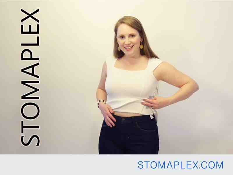 stomaplex stoma guard is well hidden under blue jeans on women with colostomy bag, she touches her stoma